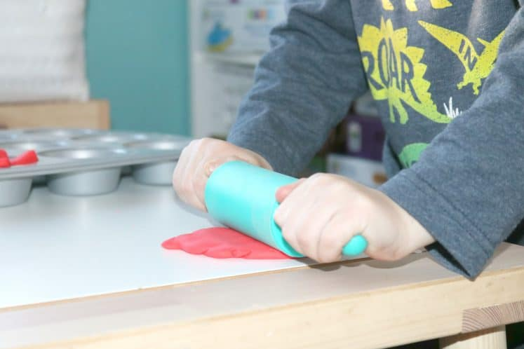 preschooler rolling playdough with rolling pin