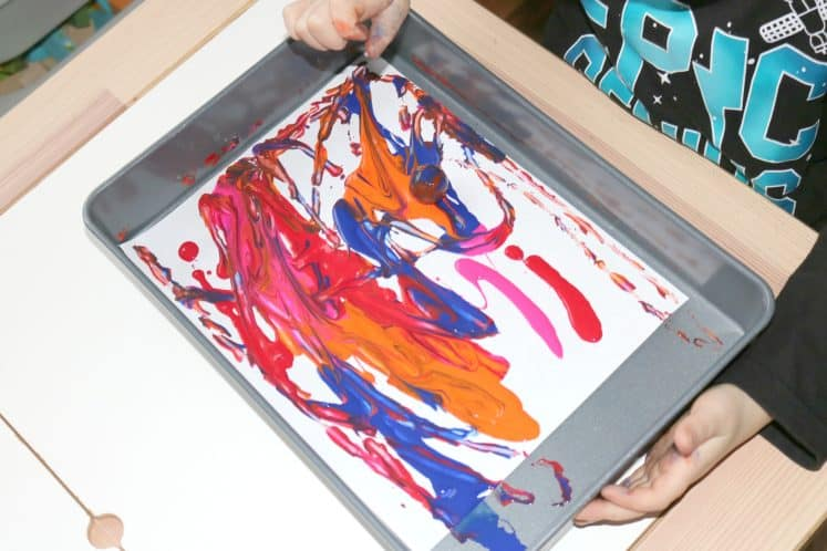 preschooler painting using cardstock, cake pan, and bounce ball
