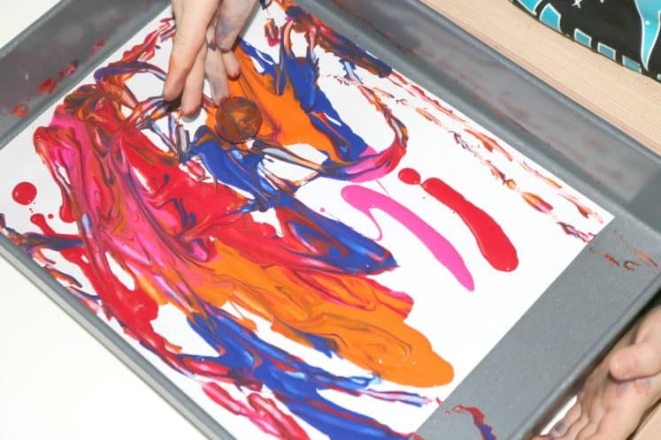 preschooler rolling ball in cake pan with paint