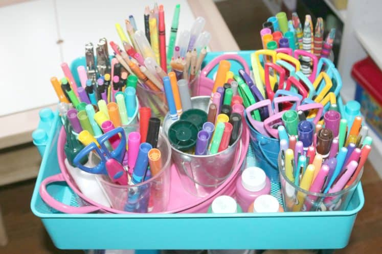 several cups filled with crayons, markers and scissors organized in an art cart