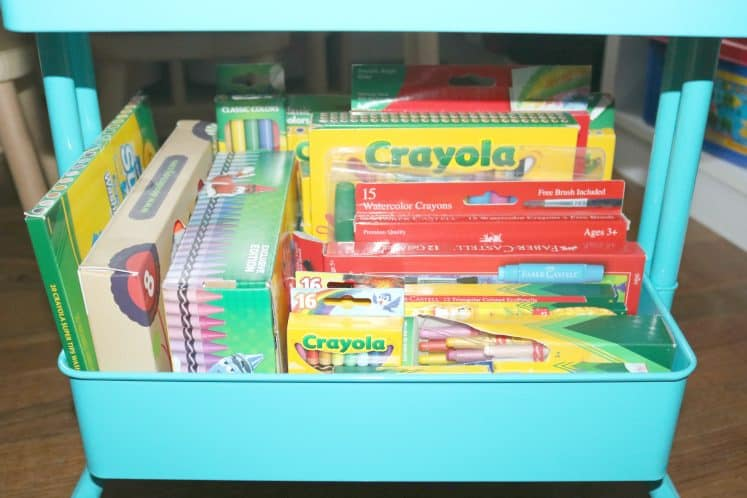 boxes of crayons, markers and colored pencils organized in an art cart