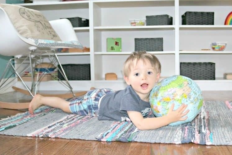 preschooler lying on rug holding inflatable globe