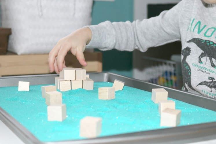 preschooler using wooden blocks to build pyramid