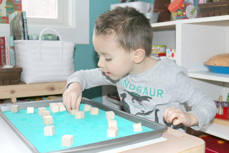 preschooler stacking wooden cubes to make pyramid