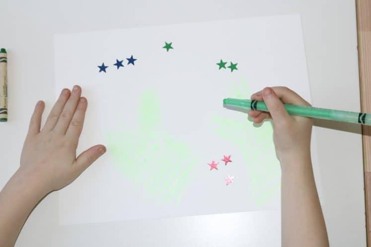 preschooler using green crayon to draw cactuses on desert night resist painting