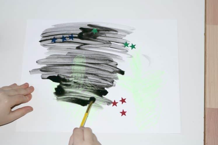 preschooler brushing black watercolor over desert night resist painting