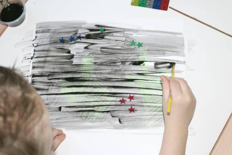 preschooler using watercolor to make desert resist painting
