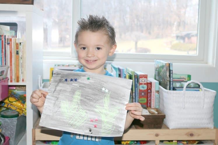 preschooler holding desert resist painting and smiling