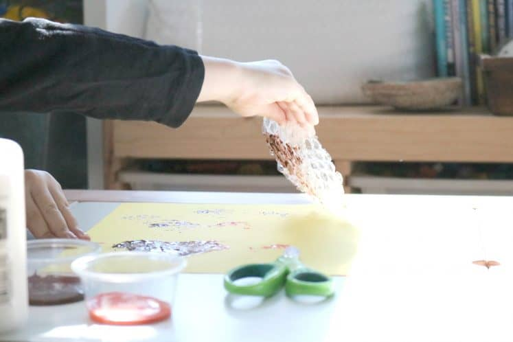 preschooler stamping using paint and bubble wrap