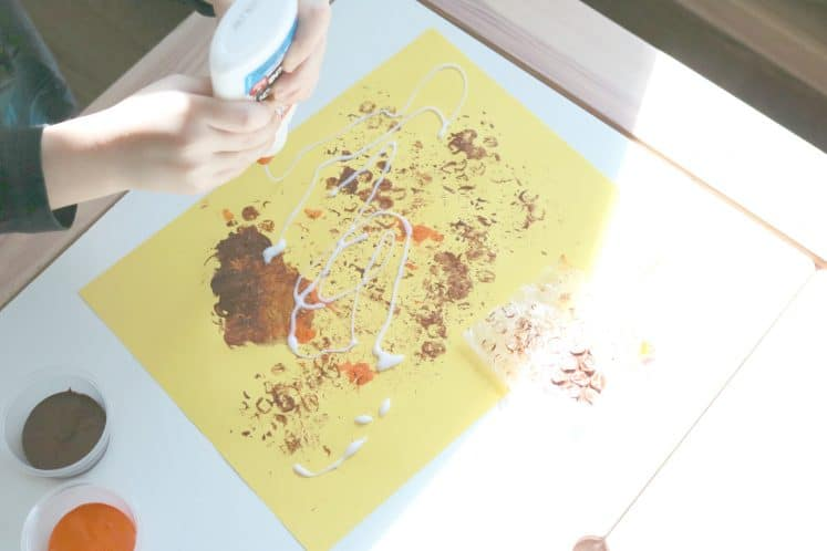 preschooler squeezing glue onto cardstock while creating beehive process art
