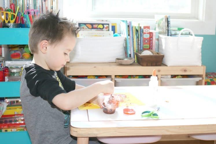 preschooler dipping bubble wrap into cup of paint