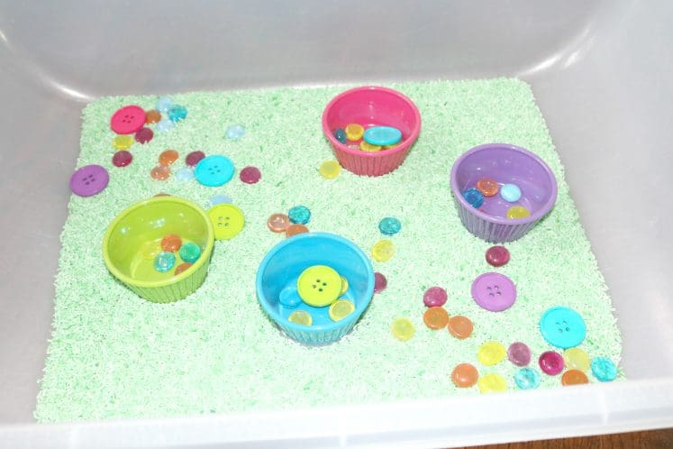 spring sensory bin with green rice, colorful buttons, and small bowls