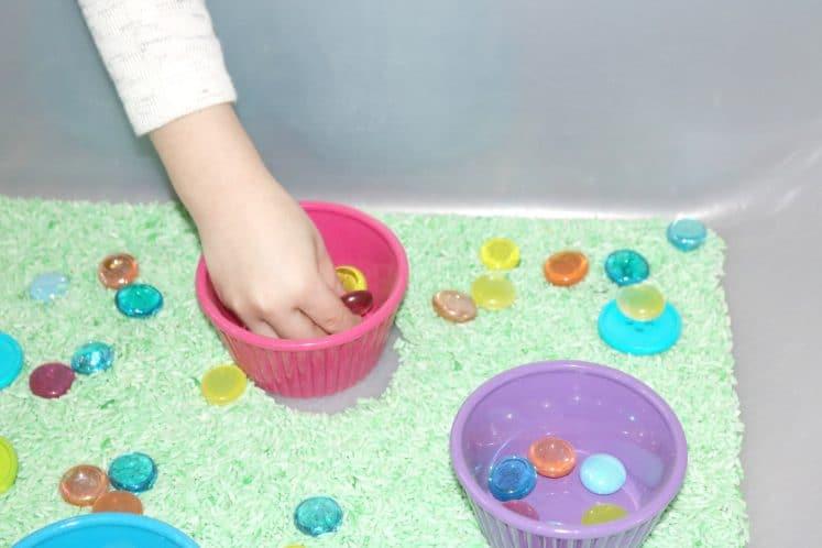 child putting colorful gemstones into spring sensory bin
