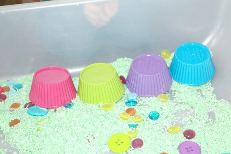 small bowls flipped over and lined up in spring sensory bin