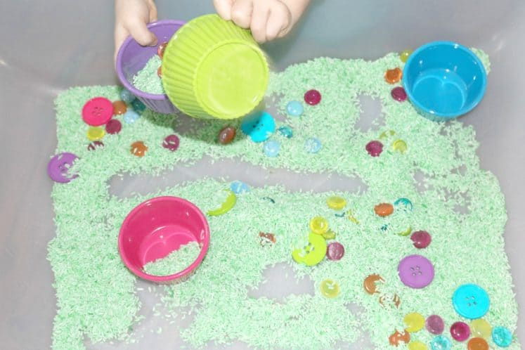 child pouring green rice and gemstones into small bowl