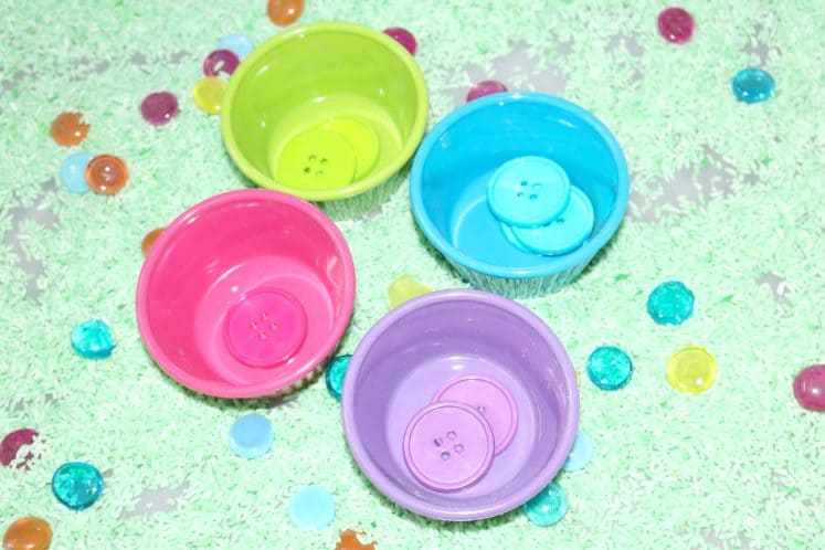 colorful bowls containing matching buttons in spring sensory bin