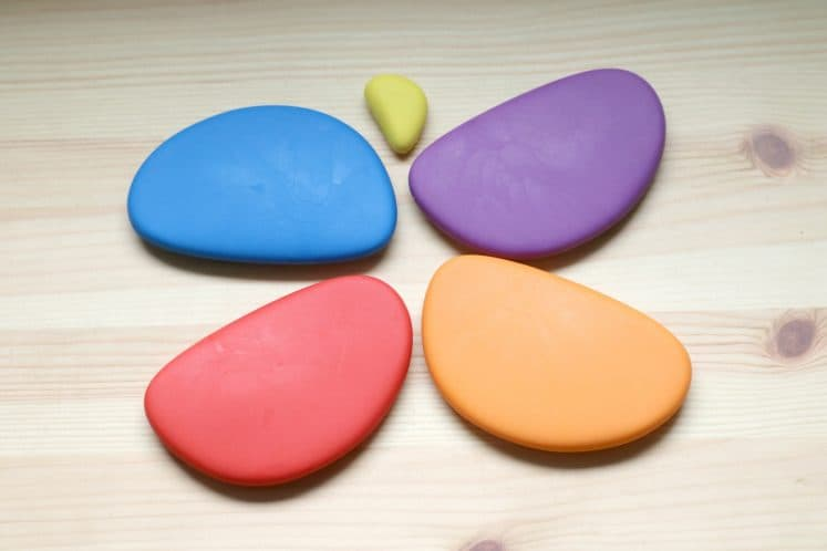 child arranging colorful stones to make butterfly shape