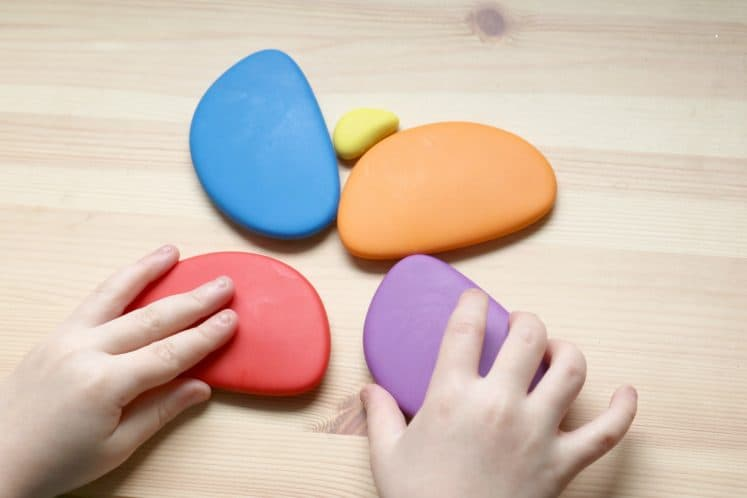 child arranging colorful stones to make butterfly designs on table