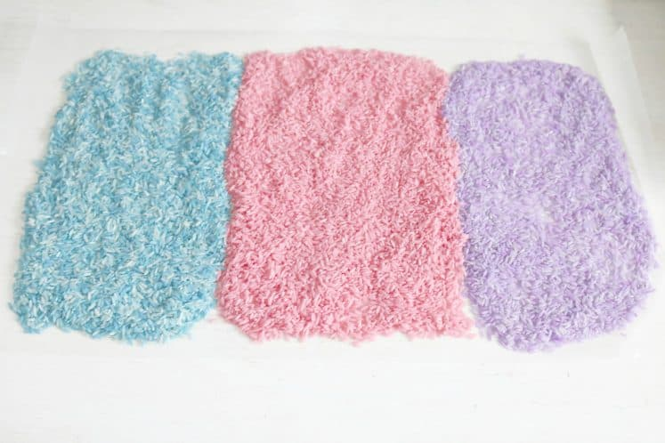 blue, pink, and purple dyed rice arranged on wax paper to dry