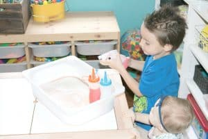 child squirting colored water into bubble play sensory bin