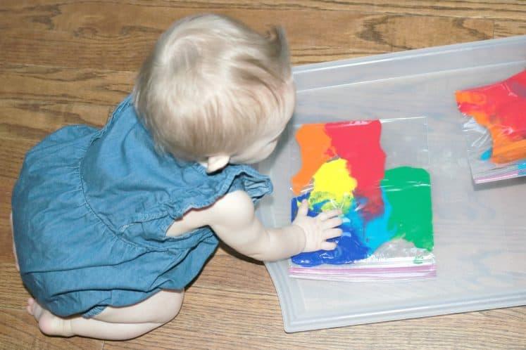 toddler pressing on rainbow sensory bag