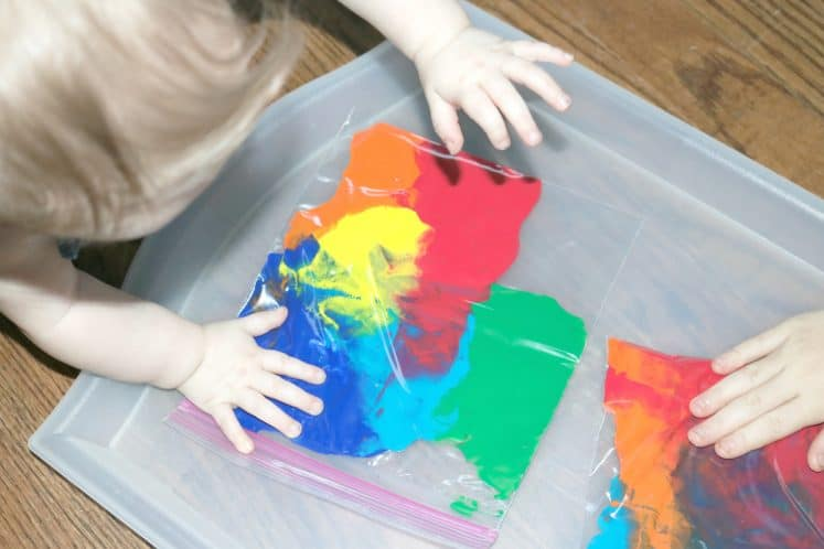 children sitting on the floor exploring rainbow sensory bags
