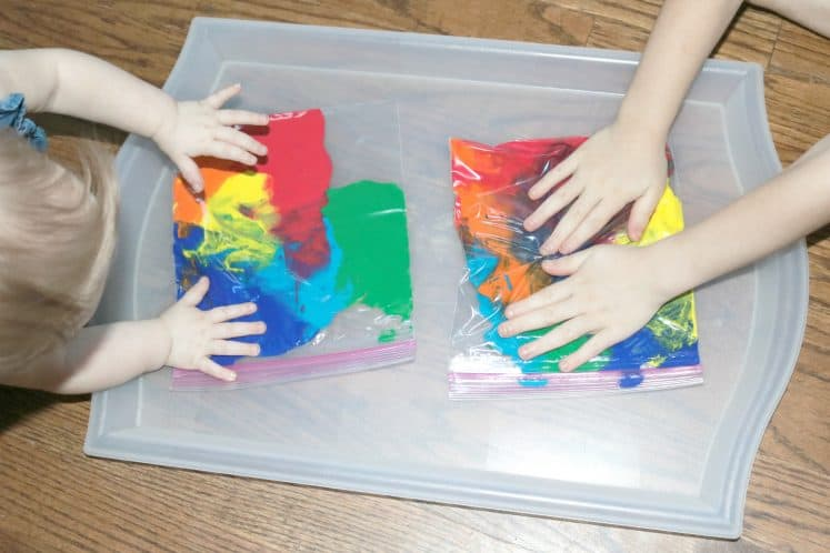 two children sitting on the floor pressing on rainbow sensory bags