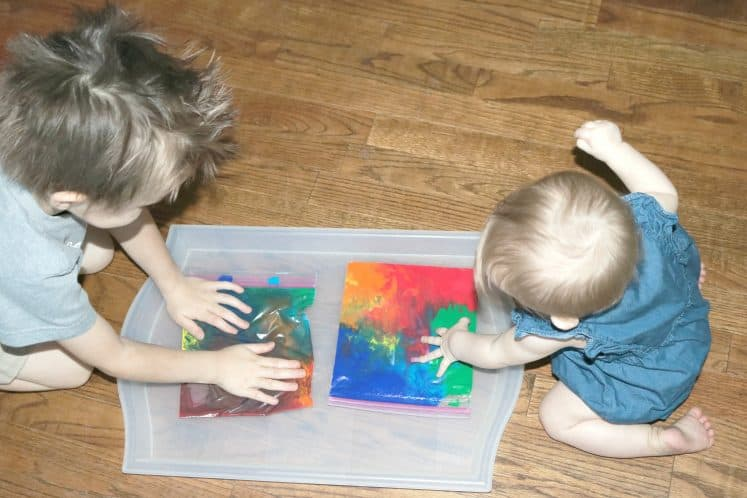 two children sitting on the floor exploring rainbow sensory bags on plastic tray