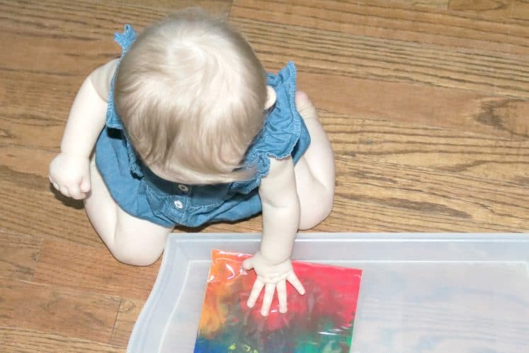 baby exploring rainbow sensory bag on floor
