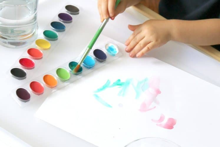 preschooler dipping paintbrush into watercolor paint