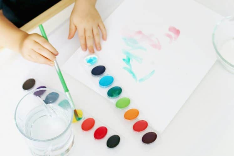 preschool dipping paintbrush in paint
