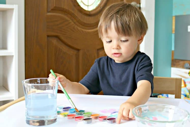 preschooler dipping paintbrush in watercolor paint