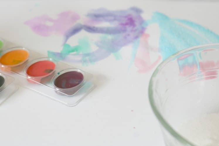 watercolor paints next to preschooler's salt painting art