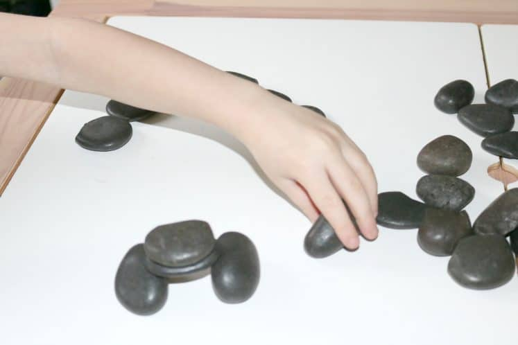 child making rock structures on table