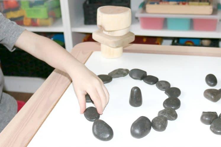 child making a circle using river rocks