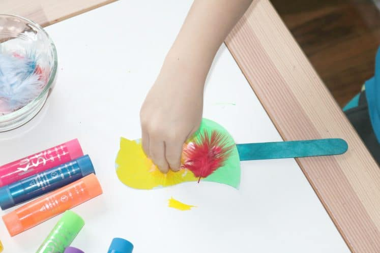 preschooler adding feathers to bird puppet craft