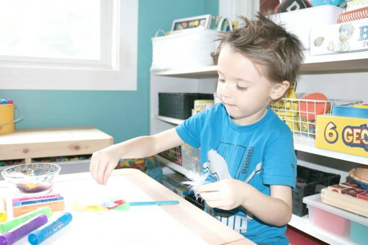preschooler putting feathers on cardstock bird