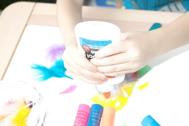 preschooler squeezing glue onto cardstock bird puppet craft