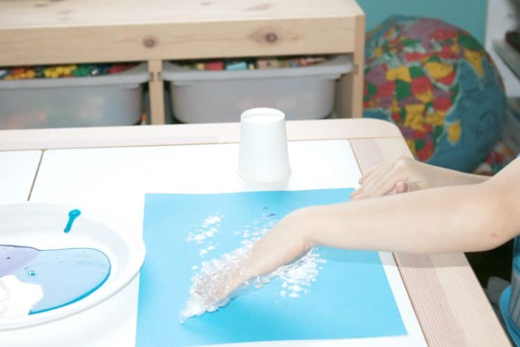 preschooler using bubble wrap to paint on blue cardstock