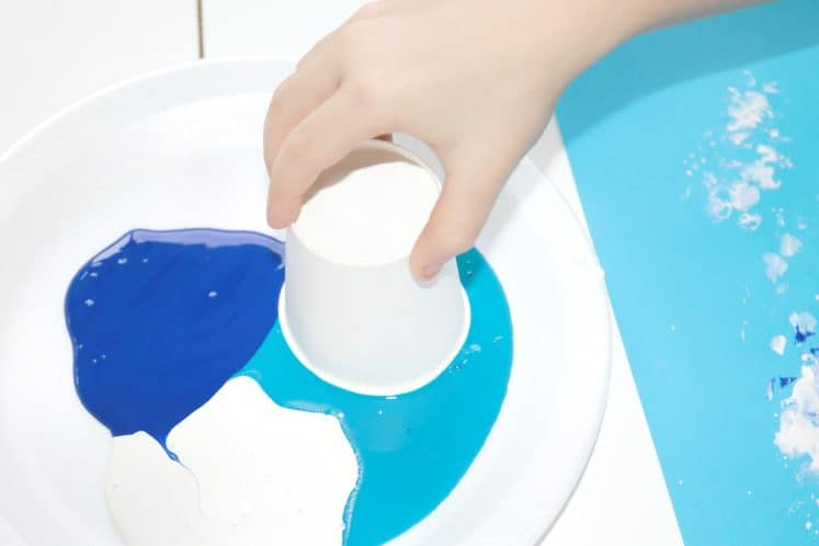 preschooler dipping paper cup in paint