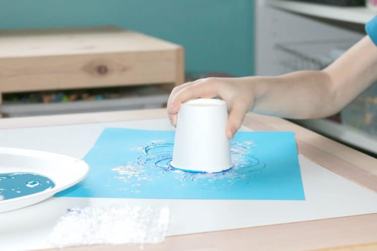 preschooler using paper cup to stamp circles on blue cardstock