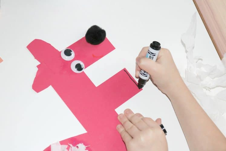 preschooler drawing paws with black marker
