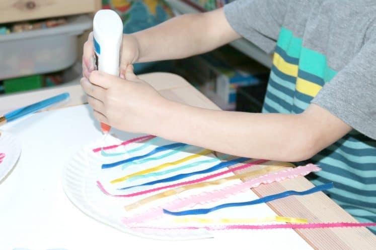preschooler squeezing glue onto jellyfish zoo craft