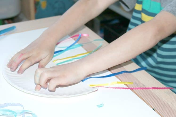 preschooler attaching the other half of paper plate to cover pieces of ribbon