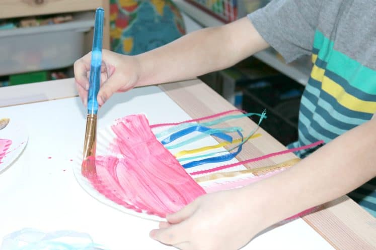 preschooler painting paper plate pink