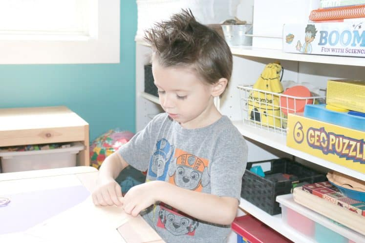 preschooler cutting cardstock to make llama craft