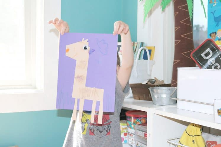preschooler holding up L is for Llama craft