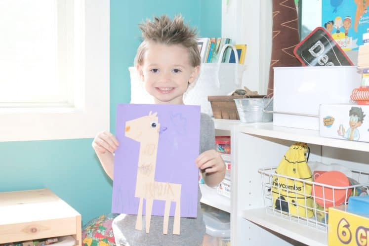 preschooler holding L is for Llama Zoo Craft and smiling