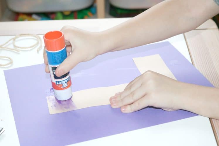 preschooler gluing cardstock L to background paper