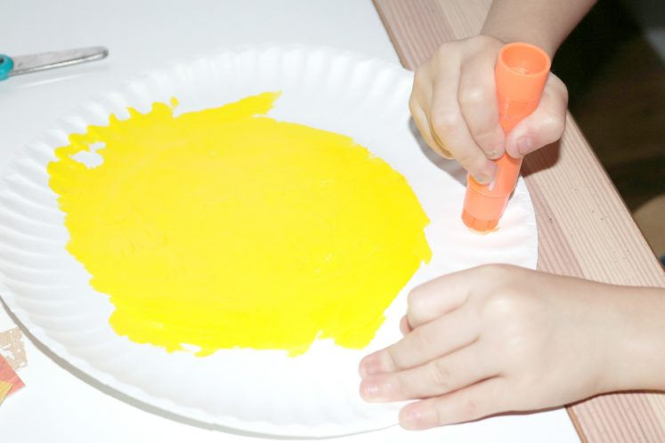 preschooler painting paper plate with orange paint stick